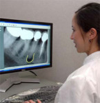 Figure 1 Dr. Lee annotates a digital radiograph on a 24-inch LCD display, with a native resolution of 1,920 by 1,200 pixels (WUXGA). Monitor size, brightness, contrast, and resolution are important components of a well-configured digital radiography syste