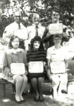 Martha McCaslin (bottom row, furthest to the right) shows a military award she received for outstanding performance during an occupational safety inspection while she was stationed in Greece.