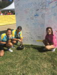 Victor Castro, CDT, at a Livestrong Austin bike race, posing with wife Angie and daughter Nicole in front of a board signed by cancer survivors.